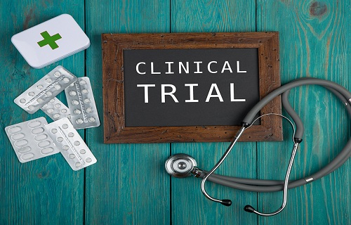 "Medecine concept - Blackboard with text ""Clinical trial"" pills and stethoscope on blue wooden background"